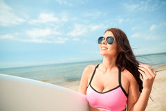 Smiling young woman with surfboard on beach Stock Photos