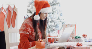 Smiling young woman surfing for Christmas bargains. Smiling young woman surfing the internet on her laptop computer for Christmas bargains as she sits at a table Stock Photography