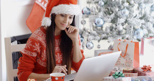 Smiling Young Woman Surfing For Christmas Bargains Royalty Free Stock Images