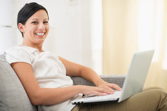 Smiling young woman surfing net on laptop Stock Photo