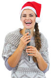 Smiling young woman in sweater and christmas hat with microphone Royalty Free Stock Photo