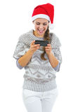 Smiling young woman in sweater and christmas hat reading sms Royalty Free Stock Photography