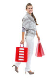 Smiling young woman in sweater with christmas shopping bags Royalty Free Stock Photography