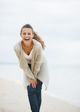 Smiling young woman in sweater having fun time on lonely beach Stock Photos