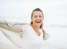 Smiling young woman in sweater having fun time on lonely beach Stock Images