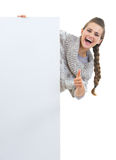 Smiling young woman in sweater looking out from blank billboard Royalty Free Stock Images