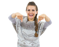 Smiling young woman in sweater pointing down on copy space Royalty Free Stock Photo
