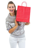 Smiling young woman in sweater showing christmas shopping bag Royalty Free Stock Images