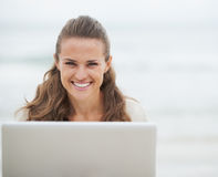 Smiling young woman in sweater sitting on beach with laptop Stock Photography