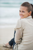 Smiling young woman in sweater sitting on lonely beach Stock Image