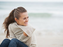 Smiling young woman in sweater sitting on lonely beach Royalty Free Stock Image