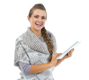 Smiling young woman in sweater using tablet pc Royalty Free Stock Images