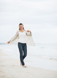 Smiling young woman in sweater walking on lonely beach Royalty Free Stock Photography