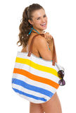 Smiling young woman in swimsuit with beach bag Stock Image