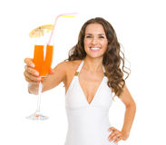 Smiling young woman in swimsuit giving cocktail Royalty Free Stock Photos