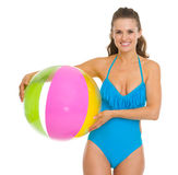 Smiling young woman in swimsuit holding beach ball Stock Photo