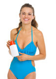 Smiling woman in swimsuit holding sun screen creme Stock Photos