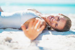 Smiling young woman in swimsuit laying on beach and greeting Stock Images