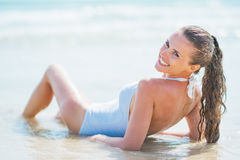 Smiling young woman in swimsuit laying at seaside. rear view Stock Images