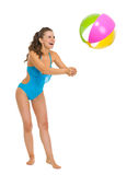 Smiling young woman in swimsuit playing with beach ball. Full length portrait of smiling young woman in swimsuit playing with beach ball isolated on white Stock Images