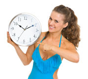 Smiling young woman in swimsuit pointing on clock Stock Photos
