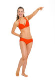 Smiling young woman in swimsuit pointing on copy space Royalty Free Stock Image
