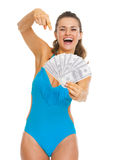 Smiling young woman in swimsuit pointing on fan of dollars Stock Photos