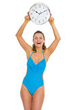 Smiling young woman in swimsuit showing clock Royalty Free Stock Photography