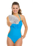 Smiling woman in swimsuit showing fan of dollars Stock Photography