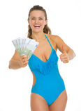 Smiling woman in swimsuit showing fan of euros Stock Images