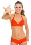 Smiling young woman in swimsuit showing starfish Royalty Free Stock Photo