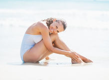Smiling young woman in swimsuit sitting on sea shore Royalty Free Stock Photo