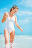 Smiling young woman in swimsuit walking at seaside Royalty Free Stock Photos
