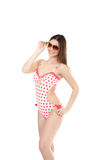 Smiling young woman in swimsuit wearing sun glasses, isolated. Smiling slim young female in polka-dotted swimsuit, red and white colored, wearing sunglasses royalty free stock photo