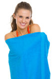 Smiling young woman in swimsuit wrapped in towel Royalty Free Stock Photography