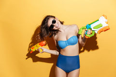 Smiling young woman in swimwear holding toys water gun Royalty Free Stock Photos