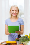Smiling young woman with tablet pc cooking at home Stock Photos
