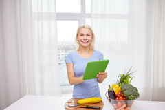 Smiling young woman with tablet pc cooking at home Stock Photo
