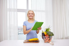 Smiling young woman with tablet pc cooking at home Royalty Free Stock Photos