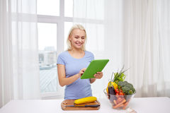 Smiling young woman with tablet pc cooking at home Royalty Free Stock Image