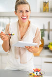 Smiling young woman with tablet pc eating fruit salad Royalty Free Stock Photography