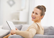 Smiling young woman with tablet pc sitting on sofa Royalty Free Stock Image