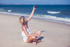 Smiling young woman take a selfie photo at sandy beach by the se stock images
