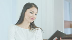Smiling young woman taking funny selfies on her tablet with her tongue out stock footage