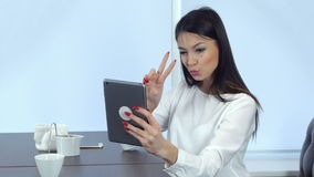 Smiling young woman taking funny selfies on her tablet sticking her tongue out stock video footage