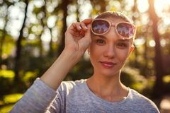 Smiling young woman taking off her sunglasses in park. Beautiful girl with natural makeup looking at camera royalty free stock photos