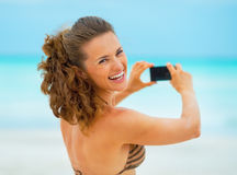 Smiling young woman taking photo on beach Royalty Free Stock Images