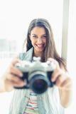 Smiling young woman taking a photo at camera Royalty Free Stock Photo
