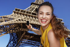 Smiling young woman taking photo with camera in Paris, France Royalty Free Stock Photo