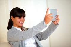 Smiling young woman taking picture with tablet pc Stock Photography